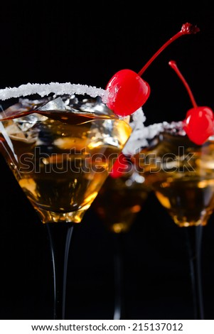cocktails with cherry and ice on black background - stock photo