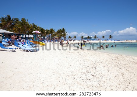 COCO CAY, BAHAMAS - MAY 26, 2015: Sandy beach with people enjoying sun and fun with their Royal Caribbean cruise ship anchored in the background - stock photo