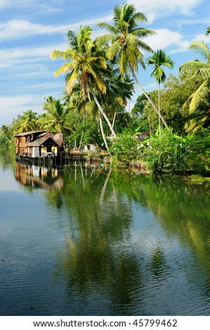 Coco trees reflection and beautifoull house boat at back waters of Kerala, India