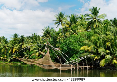Coco trees reflection and chinese fishing nets  at back waters of Kerala, India - stock photo