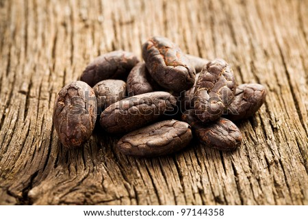 cocoa beans on old wooden desk - stock photo
