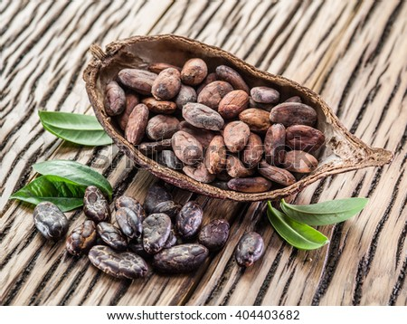 Cocoa pod and cocoa beans on the wooden table. - stock photo