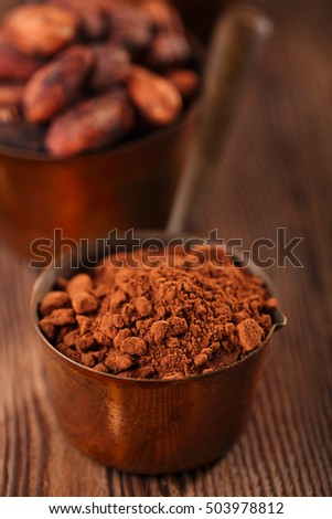 cocoa powder and grated chocolate  in vintage measuring copper pans  on old wooden background