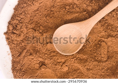 cocoa powder and wooden spoon from above - close up of textured background - stock photo