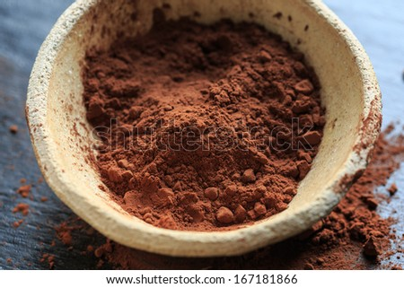 Cocoa powder in a bowl on black background, close-up - stock photo