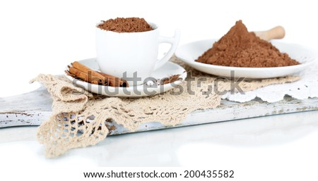 Cocoa powder in cup on napkin on wooden board isolated on white - stock photo