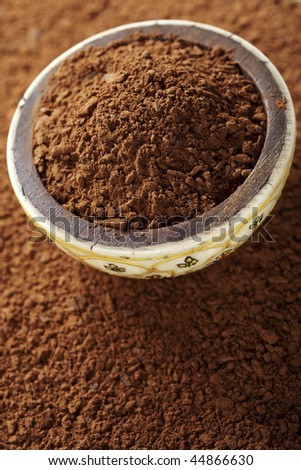 cocoa powder with small pieces of chocolate in bowl, on its background - stock photo