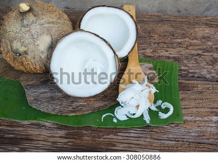 coconut and copra with spoon on wooden background