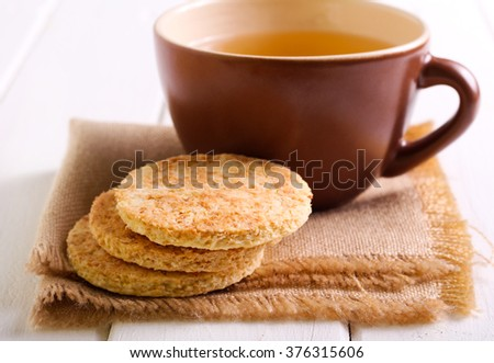 Coconut biscuits and cup of tea on napkin