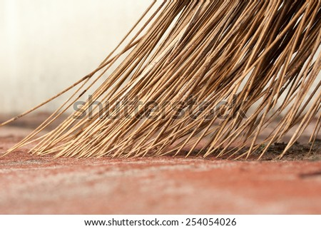 Coconut broom stick surrounded by dust and sand - stock photo