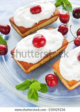 Coconut cakes with whipped cream and sweet cherry. Shallow dof.