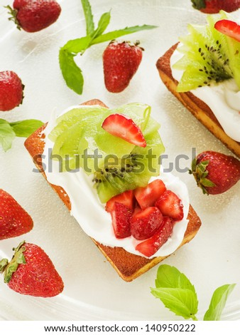 Coconut cakes with whipped cream, strawberry and kiwi. Shallow dof.