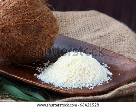 Coconut chips and coconut on the wooden plate - stock photo