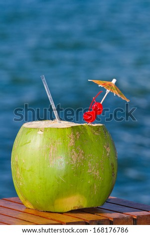 coconut drink served in a green coconut with rum and juices served on the beach of Belize - stock photo