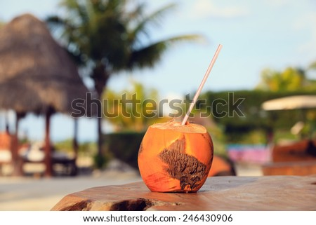 coconut drink with straw in tropical cafe on the beach - stock photo