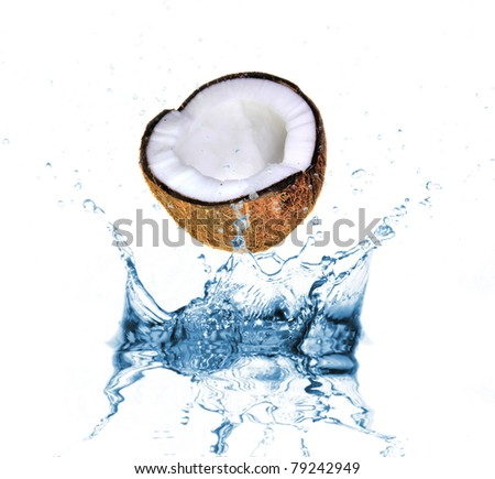 Coconut dropped into water splash on white - stock photo