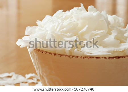 Coconut flakes overflowing from decorative ceramic bowl onto wood table.  Macro with extremely shallow dof.