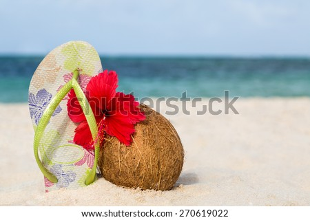 Coconut, hibiscus flower and flip flops on the beach - stock photo