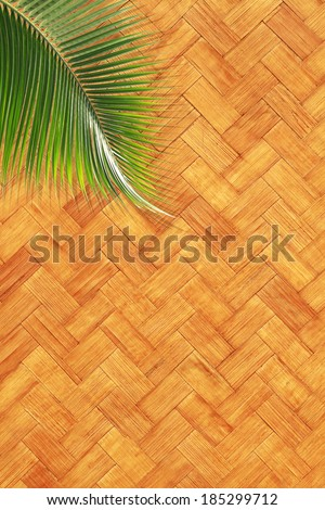 Coconut leaf over wicker woven texture background - stock photo