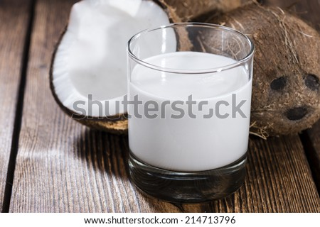 Coconut Milk in a glass on dark wooden background (close-up shot) - stock photo