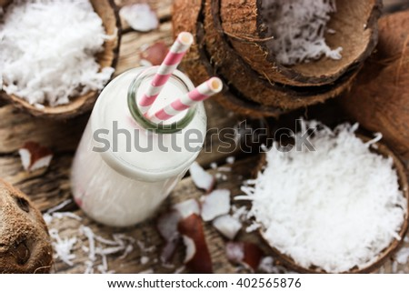 Coconut milk in bottle and fresh coconut chips on wooden table selective focus - stock photo