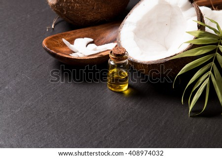 coconut oil and fresh coconuts on black stone  - stock photo