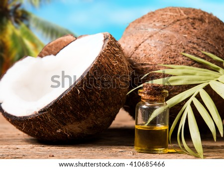 coconut oil and fresh coconuts on black stone with tropical beach background - stock photo