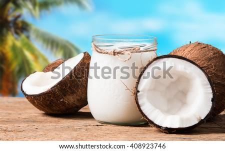 coconut oil and fresh coconuts on old wooden table with tropical beach background - stock photo