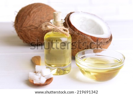 Coconut oil on table on light background - stock photo