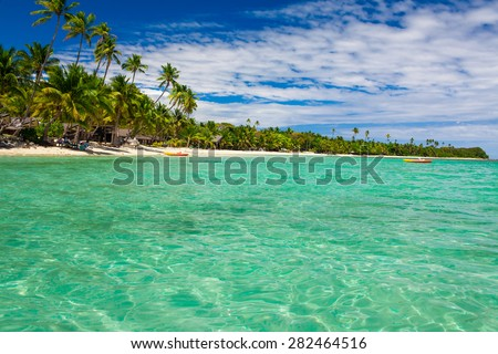 Coconut palm trees over tropical lagoon on Fiji Islands - stock photo