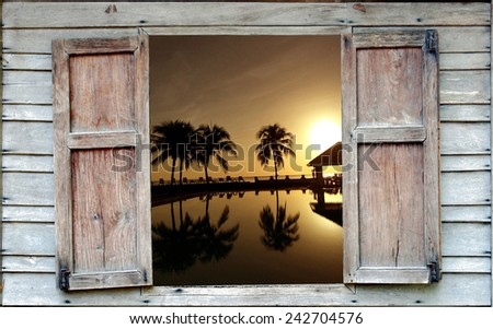 Coconut palms on sand beach in tropic on sunset - stock photo