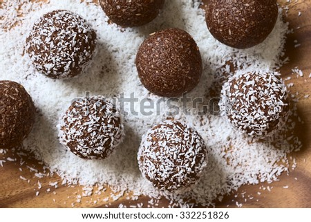 Coconut rum balls being covered with grated coconut on wooden plate, photographed overhead with natural light (Selective Focus, Focus on the top of the balls) - stock photo