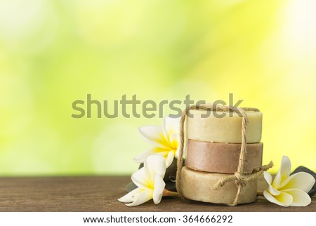 coconut soap, mangosteen soap, rice milk soap placed on a wooden table with frangipani and natural background. Spa concept. - stock photo