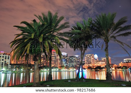 Coconut tree and Orlando downtown skyline over Lake Eola at dusk with urban skyscrapers and lights. - stock photo