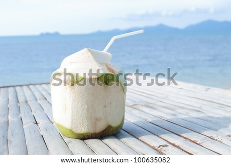 Coconut Water Drink on bamboo table with sea background - stock photo