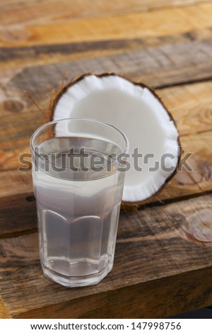 Coconut water. Full glass of fresh coconut juice and coconut on wooden table. Shallow depth of field.