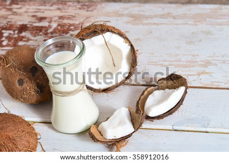 Coconut with coconut oil in jar on white wooden background