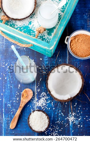 Coconut with coconut oil, water and sugar and coconut flakes on a wooden turquois background - stock photo