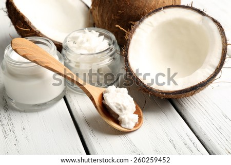 Coconut with jars of coconut oil and cosmetic cream on wooden background - stock photo