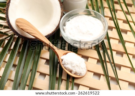 Coconut with leaf and coconut oil in bowl on wooden background - stock photo