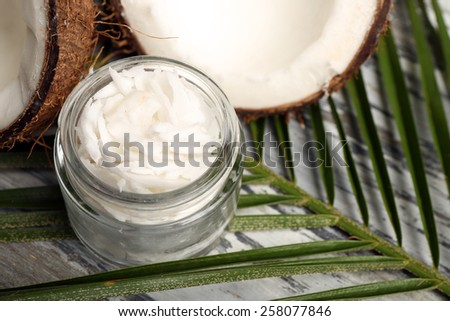 Coconut with leaf and jar of coconut oil on table close up - stock photo