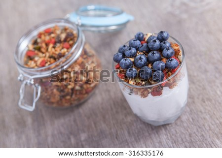 Coconut yogurt topped with grain free  granola made with mixed nuts, seeds, raisins, with blueberries on the top, selective focus - stock photo
