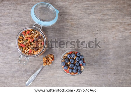 Coconut yogurt topped with grain free oat free paleo muesli made with mixed nuts, seeds, raisins, with blueberries on the top, above view - stock photo