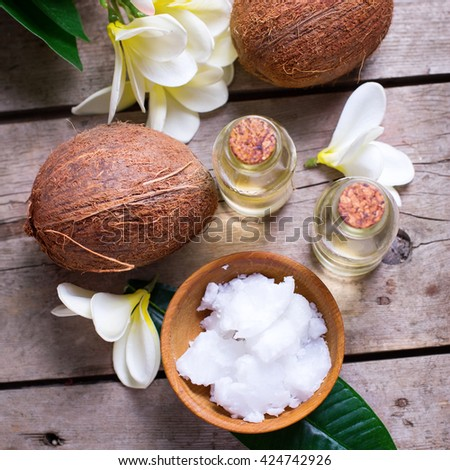 Coconuts and coconut oil on  vintage wooden background. Selective focus. Flat lay. Natural organic spa products. Square image. - stock photo