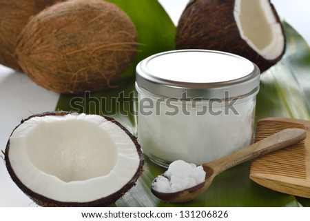 Coconuts and organic coconut oil in a glass jar on white background. Hair treatment. - stock photo