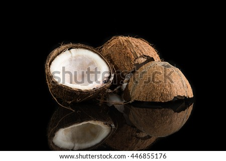 Coconuts shells on black background - stock photo