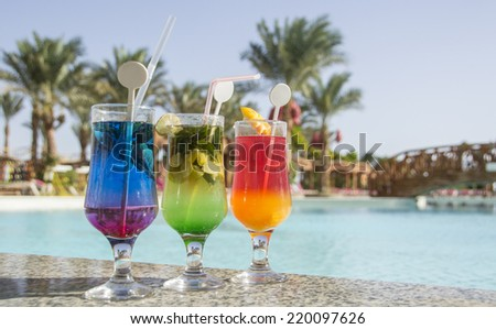 cocotail drinks by tropical swimming pool - stock photo