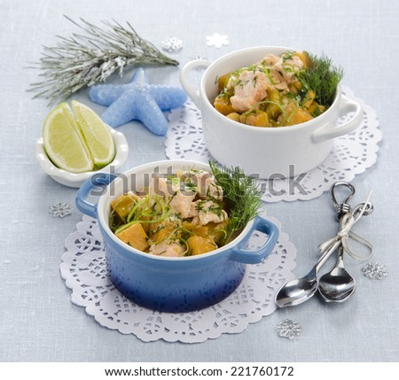 cocotte with vegetables and salmon pumpkin peel of lime on the holiday table with a blue tablecloth with candles - stock photo