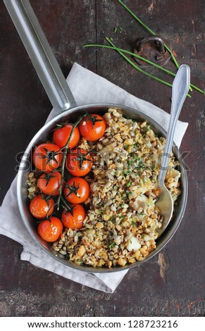 Cod fillet crumble with sesame seeds, sunflower seeds, flax seeds, pine nuts and fresh chopped chives with roasted cherry tomatoes in a pan - stock photo