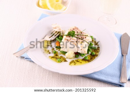 Cod fillet with green beans, peas, parsley, olive oil, wine, close up